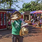 North America, Latin America, Latin, Caribbean, tropical, Mexico, Yucatan, Chichen Itza, Xchen Itza, Maya, Mayan, UNESCO World Heritage Site,Man selling his wares to tourists at historic Chichen Itza.