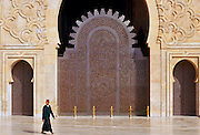 Muslim man wearing traditional fez hat walking by Hassan II Mosque in Casablanca, Morocco