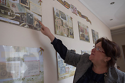 Victoria Mochalova Alexandrovna, the director of the Lugansk Orphanage No.1 points to a photograph of herself and her parents in Moscow's Red Square which form part of a display dedicated to Russian history on the walls of the orphanage in Lugansk.