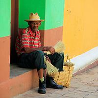 Central America, Cuba, Trinidad. Cuban man sitting on stoop in Trinidad.