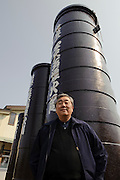 """CEO Masanori Honda stands in from of a launching tube for a """"yonshakudama"""" firework in front of Katakai Fireworks Co., Ltd, Katakai, Japan, April 7, 2009. The company makes the world's largest firework, a 120cm round shell called a """"yonshakudama""""."""