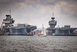 © Licensed to London News Pictures. 02/07/2020. Portsmouth, UK.  A lone yacht sails near Royal Navy aircraft carriers HMS Queen Elizabeth (R) and her sister ship HMS Prince of Wales in Portsmouth harbour. The 65,000 tonne supercarrier has been at sea for 10 weeks conducting trials of the new F35 Lightening fighter jets ahead of her first operational mission in 2021. Photo credit: Peter Macdiarmid/LNP
