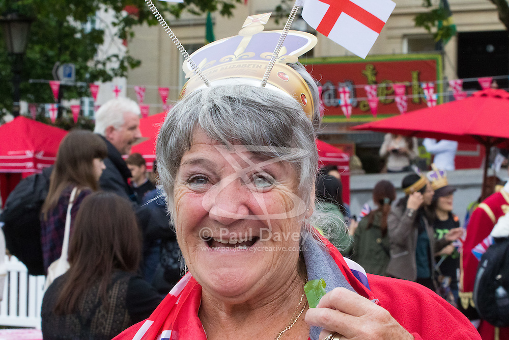 Trafalgar Square, London, June 12th 2016. Rain greets Londoners and visitors to the capital's Trafalgar Square as the Mayor hosts a Patron's Lunch in celebration of The Queen's 90th birthday. PICTURED: A woman smiles for the camera as the rain abates.