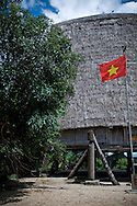 Traditional architecture of a Bahnar ethnic stilt house with a straw roof raising high. Pleiku area, Vietnam, Asia. A vietnamese flag flies in the yard.