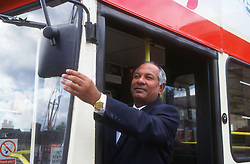 Male bus driver adjusting mirror of double decker bus,