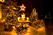 Glowing angel in snow under a star in front of a residential home. St Paul Minnesota USA