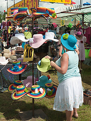 Woman choosing a hat at a stall at WOMAD 2009