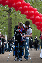 © licensed to London News Pictures. London, UK 08/05/2012. Claire Lomas, who paralysed from the chest down after an accident, finishes the London Marathon and walking with her husband Dan Spincer, today after 16 days with a robotic suit to raise money for Spinal Research (08/05/12). Photo credit: Tolga Akmen/LNP