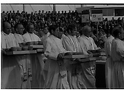 Pope John-Paul II visits Ireland..1979..29.09.1979..09.29.1979..29th September 1979..Today marked the historic arrival of Pope John-Paul II to Ireland. He is here on a three day visit to the country with a packed itinerary. He will celebrate mass today at a specially built altar in the Phoenix Park in Dublin. From Dublin he will travel to Drogheda by cavalcade. On the 30th he will host a youth rally in Galway and on the 1st Oct he will host a mass in Limerick prior to his departure from Shannon Airport to the U.S..Image of the clergy as the move to their designated positions to distribute the Hosts to the congregation.