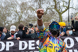 © Licensed to London News Pictures. 20/03/2021. London, UK. A person wearing a mask and goggles raises a fist on Park Lane during the anti-lockdown demonstration 'Worldwide Rally For Freedom' held in central London. Photo credit: Peter Manning/LNP