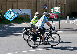 © Licensed to London News Pictures. 14/09/2019. Felton, North Somerset, UK. Cyclists circle the roundabout and around the roads outside of Bristol Airport for an Extinction Rebellion protest against the proposed expansion plans for Bristol Airport. The campaigners say that there will be more air pollution from increased flights which are not counted in the airport's target to be carbon neutral by 2025, that there will be a loss of greenbelt land, more noise pollution from more flying, traffic congestion, and ill health from respiratory and cardiac disease. Campaigners say a recent report found that the incidence of asthma and respiratory diseases was on average 17% higher among those living within 6.2 miles of a major airport and that cardiac diseases were 9% more common. Photo credit: Simon Chapman/LNP.