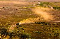 A safari vehicle trailed by dust, Amboseli National Park, Kenya