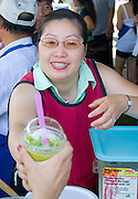 Hmong woman serving cup of fruit drink at outdoor cafe. Hmong Sports Festival McMurray Field St Paul Minnesota USA