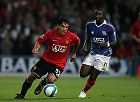 Photo: Lee Earle.<br /> Portsmouth v Manchester United. The FA Barclays Premiership. 15/08/2007.United's Carlos Tevez(L) sprints away from Pompey's Sulley Muntari.