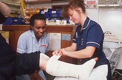 Nurse and nursing auxiliary bandaging patient's injured leg,