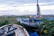 Multi-coloured ribbons hang from the mast of a small covered yacht that sits on beach shingle, on a low-tide evening sunset, on 27th July 2021, in Whitstable, Kent, England.