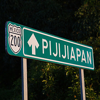 A signpost to Pijijiapan on the road before dawn. Migrants began walking before 3am, to avoid time in the heat on the road