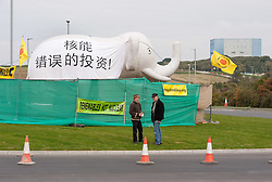 "© Licensed to London News Pictures. 19/10/2015. Hinkley Point, Somerset, UK.  Anti-nuclear campaigners Theo Simon and Trevor Houghton at protest by the group ""Osborne's Folly"" (after the Chancellor George Osborne), protesting against the proposed new nuclear power station Hinkley C and against Chinese investment in the project.  The group has occupied a roundabout near the site and erected an inflatable white elephant with a banner written in Chinese and say they want to send a message to the visiting Chinese President Xi Jinping that EDF's Hinkley C would be ""a bad investment"" for the Chinese state. They say that the stalled project has become ""Osborne's Energy Folly"" and should now be abandoned.  Theo Simon, one of the campaigners said: """"Ironically, the Chinese are leading the world in renewable energy investment in their own country, where there is also a growing anti-nuclear movement"". Photo credit : Simon Chapman/LNP"