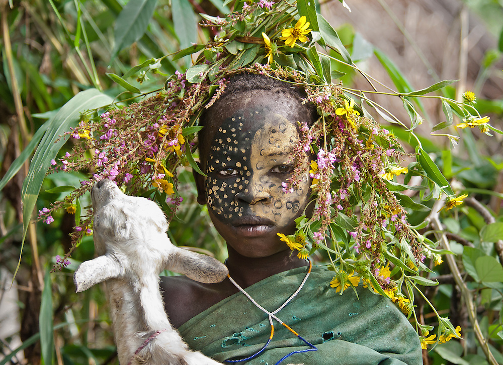 A young girl from the Mursi tribe with her goat. The goat kept eating at the girl's headdress while she was trying to pose. It made for a good laugh for everyone. <br /> Omo Valley, Ethiopia