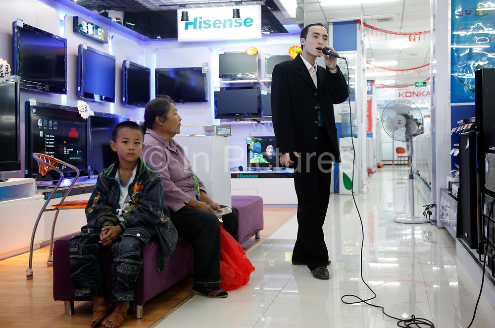 Cheng Zhifang, self proclaimed top salesman at the Yingfeng Electronics Store, demonstrate the use of a  karaoke machine to a rural woman with a child in Daoxian, Hunan Province, China, on Saturday, 16 October 2010.
