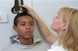 Health care assistant measuring height of patient during routine general checkup in community paediatric health centre,