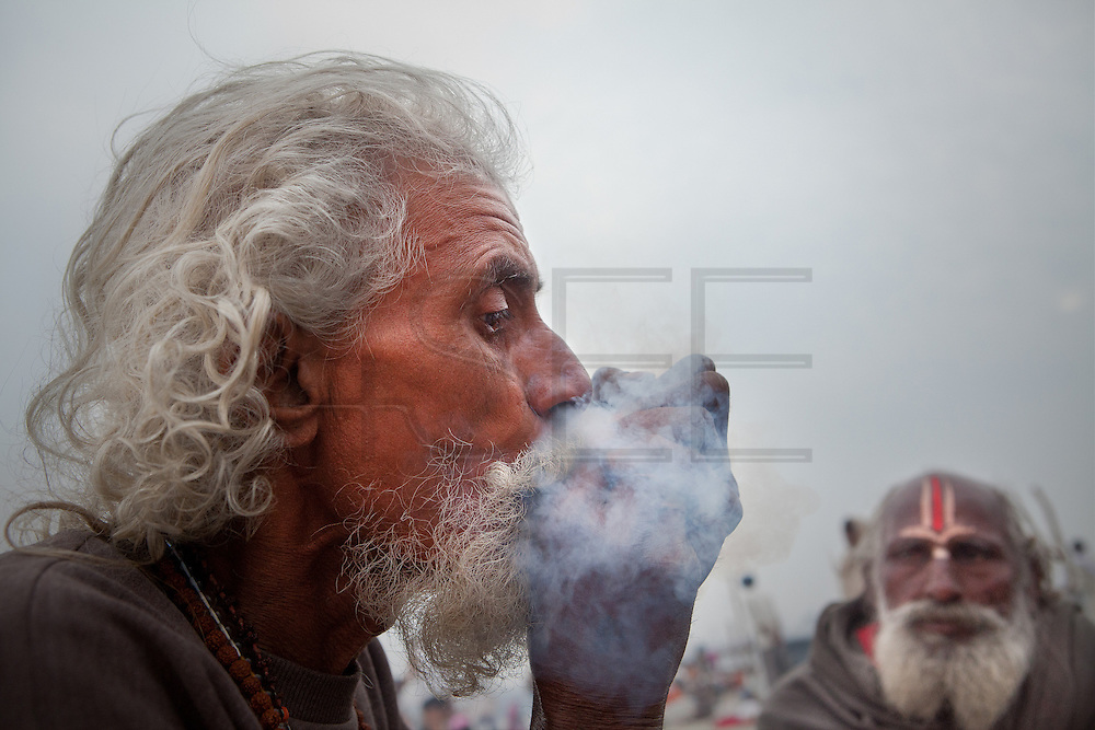 Sadhus smoking hashish. February 2013, Allahabad. //The Maha Kumbh Mela is believed to be the single largest religious gathering in the world. It's a sacred pilgrimage celebrated every twelve years. In 2013 it has taken place in Allahabad, in the confluence of the rivers Ganga, Yamuna and Saraswati. Millions of hindu people gather on a single day for a ritual bath in the sacred waters of Ganga. The event congregate millions of devotees, sadhus and sadhvis of all the akharas coming from all over India.