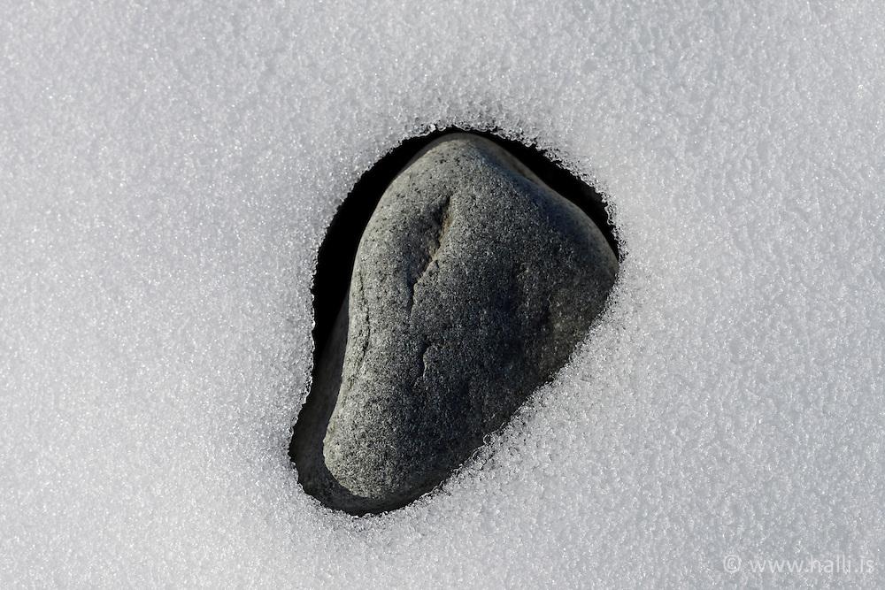 Stone and metling snow in  sand beach below Jokulsarlon, Iceland-  steinn í bráðnandi snjó í sandfjöru neðan við Jökulsárlón