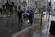 Storm Georgina swept across parts of Britain and in central London, lunchtime office workers were caught out by torrential rain and high winds, on 24th January 2018, in London, England. Pedestrians resorted to leaping across deep puddles at the junction of New Oxford Street and Kingsway at Holborn, the result of overflowing drains. Third in a sequence of seven photos.