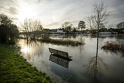 © Licensed to London News Pictures. 22/12/2019. Thames Ditton, UK. A flooded park bench on the edge of The River Thames which has burst it's banks at Thames Ditton, Surrey. Further weather warnings are in place following flooding and high winds in parts of the UK . Photo credit: Ben Cawthra/LNP