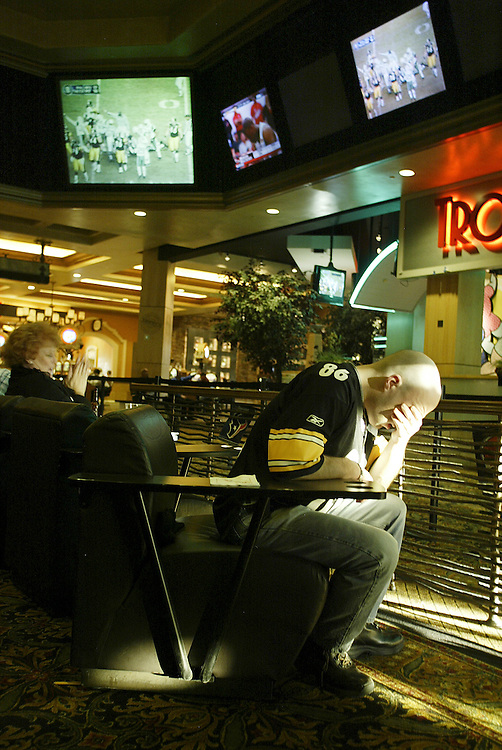 LAS VEGAS, NV - JANUARY 15:  One Pittsburgh Steeler fan can barely take watching his team struggle against the New York Jets in final action in the sports book inside the Green Valley Ranch Resort and Spa in Las Vegas on January 15, 2005. Sports Illustrated rated the sports book, complete with oversize, leather chairs, as one of the top places in the country to watch sports. (Photo by Todd Bigelow/Aurora)