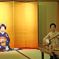 Asia, Japan, Kyoto. Geisha dancer and musician perform to dinner guests.