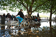 Woman cycles through a deep puddle under trees after heavy rain on the riverside walkway. The South Bank is a significant arts and entertainment district, and home to an endless list of activities for Londoners, visitors and tourists alike.