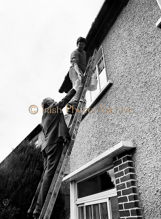 Austin Currie going to great heights to meet John Doyle as he canvasses in Palmerstown, in his quest to win a seat for Fine Gael in the General Election. Currie, a founder member of the SDLP, previously held a seat in the Northern Ireland Executive, serving as Minister for Housing and Local Planning.<br /> 7 June 1989