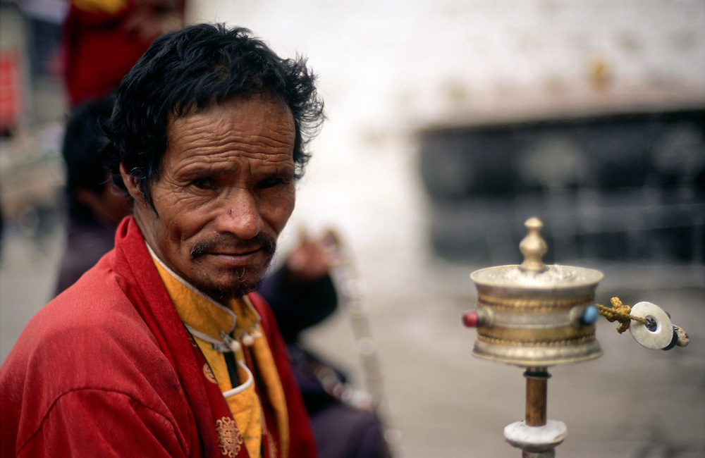 A pilgrim sits praying with a prayer wheel outside the Jokhang Temple, the most sacred site in Tibetan Buddhism. Lhasa, Tibet. 2005.