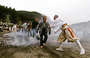 A Yamabushi or mountain priest  helps people walk across the embers of a large bonfire of ceder branches in the Hi Watari, fire walking, festival of Takao san Guchi near Tokyo, Japan. Sunday March 11th 2007