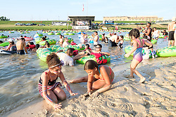 """People in floating tubes in the Trinity River listening to live music and playing in the river at the """"Rockin' the River"""" July 4th celebration on  the Trinity Trails at the Panther Island Pavilion, Fort Worth, Texas, USA."""