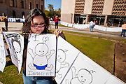 """07 FEBRUARY 2011 - PHOENIX, AZ: JULISSA VILLA, from Tucson, AZ, stands in support of birthright citizenship in front of the Arizona Capitol with a chain of hand drawn babies that represent """"anchor babies"""" Monday, February 7.The Arizona State Legislature, led by the State Senate is debating the 14th Amendment, which would bar US citizenship for children born in the US to undocumented immigrants. The bill has broad support among Republicans, who are the majority party, in the state legislature but not among Democrats. The law is also very unpopular in the state's Latino and immigrant communities.          Photo by Jack Kurtz"""