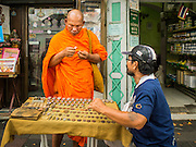 08 JANUARY 2015 - BANGKOK, THAILAND:  A Buddhist monk looks at amulets in a street side stall. Hundreds of vendors sell amulet and Buddhist religious paraphernalia to people in the Amulet Market, an area north of the Grand Palace near Wat Maharat in Bangkok.            PHOTO BY JACK KURTZ