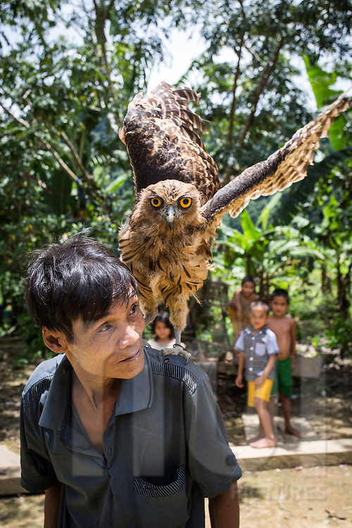 A man from Ban Doong ethnic village carries on his shoulders a domesticated owl, Phong Nha-Ke Bang National Park, Quang Binh Province, Vietnam, Southeast Asia