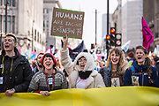 A woman dressed in a  furry coat holds up a placard while singing during a protest against climate change in the middle of Oxford Circus on 15th April, 2019 in London, United Kingdom.  Extinction Rebellion have blocked five central London landmarks in protest against government inaction on climate change. .