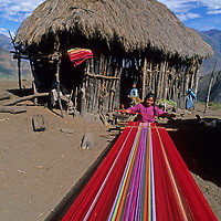 A young woman weaves fabric at her family's homestead in the Cordillera Vilcabamba, Peru.