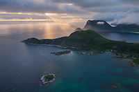 Rays of sunlight sine over coastal mountains from Offerøykammen, Vestvågøy, Lofoten Islands, Norway