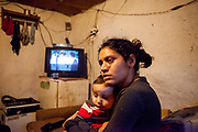 Klara (22) holding her little son Kristian who was ill in this time, in their hut at the Roma settlement in Ostrovany.