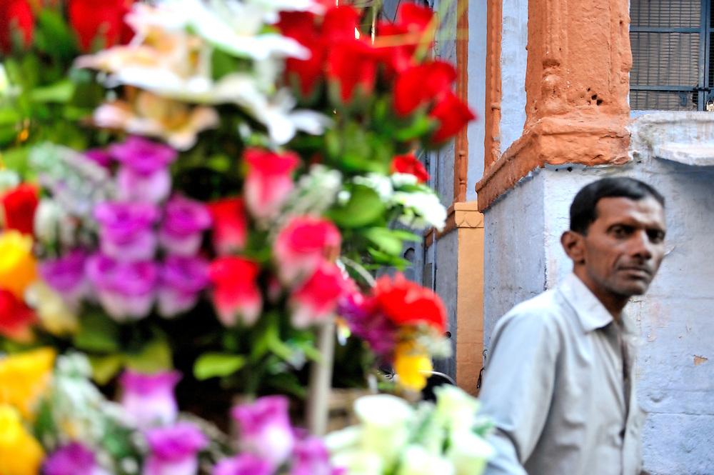 Man behind a display of flowers