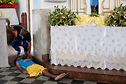 Homless disabled man lying on the floor next to the altar. Often the lines between Candomble and Catholicism are blurred. This is especially true with the Sao Lazaro event in late January in Salvador, Bahia, Brazil, the city which is known as the home of Candomble. Sao Lazaro represents healing and the sick.