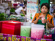 17 MAY 2013 - BANGKOK, THAILAND:   A sweetened drink and dessert vendor waits for customers in the flower market in Bangkok. The Bangkok Flower Market (Pak Klong Talad) is the biggest wholesale and retail fresh flower market in Bangkok. It is also one of the largest fresh fruit and produce markets in the city. The market is located in the old part of the city, south of Wat Po (Temple of the Reclining Buddha) and the Grand Palace.   PHOTO BY JACK KURTZ