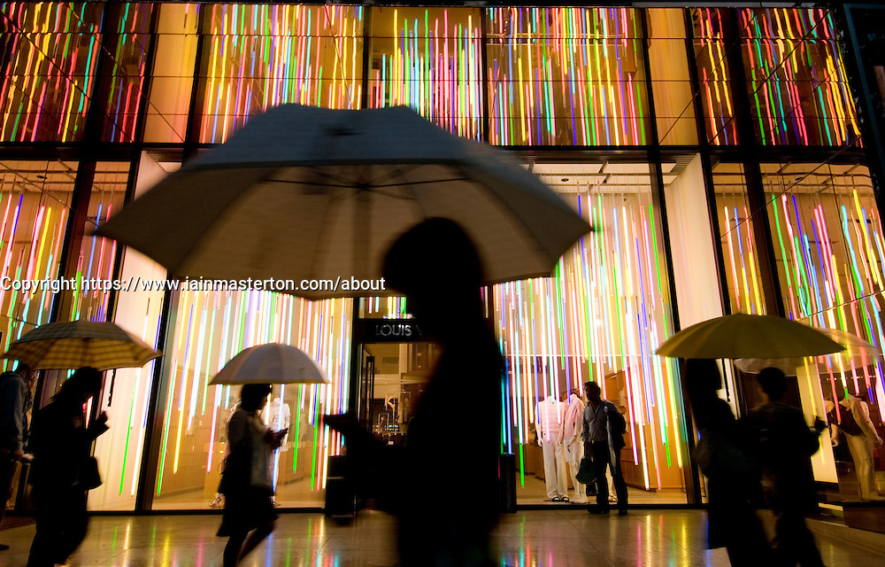 Exterior night view of Louis Vuitton store in rainy weather with people holding umbrellas in Tokyo Japan