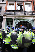 Anti capitalists / anarchists go on the rampage on the back of the peaceful TUC protest march on 26th March 2011 in London, United Kingdom. The masked demonstrators ran a twisting route through the capital confusing the police and creating a situation which was very difficult to manage. The protesters attacked banks, shops and hotels, and the police in riot gear fought  face to face with them as they were pelted with ammonia, paint and fireworks loaded with coins.
