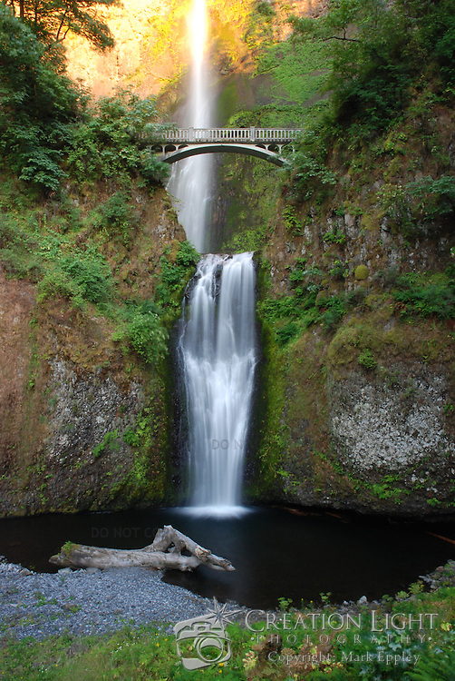 Multnomah Falls is a waterfall on the Oregon side of the Columbia River Gorge. The falls drops in two major steps, split into an upper falls of 542 feet (165 m) and a lower falls of 69 feet (21 m). The total height of the waterfall is 620 feet (189 m) making it the tallest waterfall in the State of Oregon.