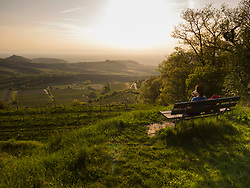 Woman hiker taking rest and admiring scenic view of mount Kaiserstuhl, Baden-Wuerttemberg, Germany